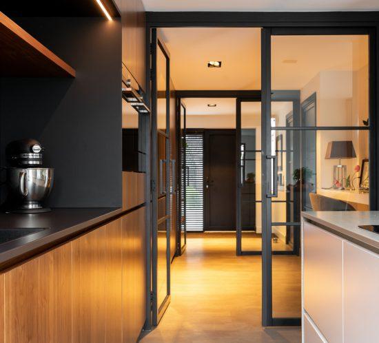 Glazen deuren en een houten kastenwand van warm notenhout in Tuitjenhorn